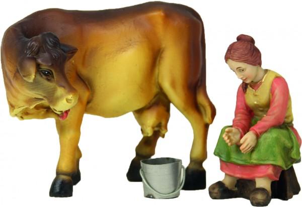 Bäuerin mit Kuh beim Melken